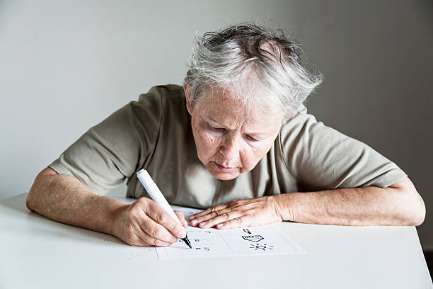 Illiterate woman learning to write Illiterate woman is learning how to write, sitting at table, learning material in spanish language illiteracy stock pictures, royalty-free photos & images