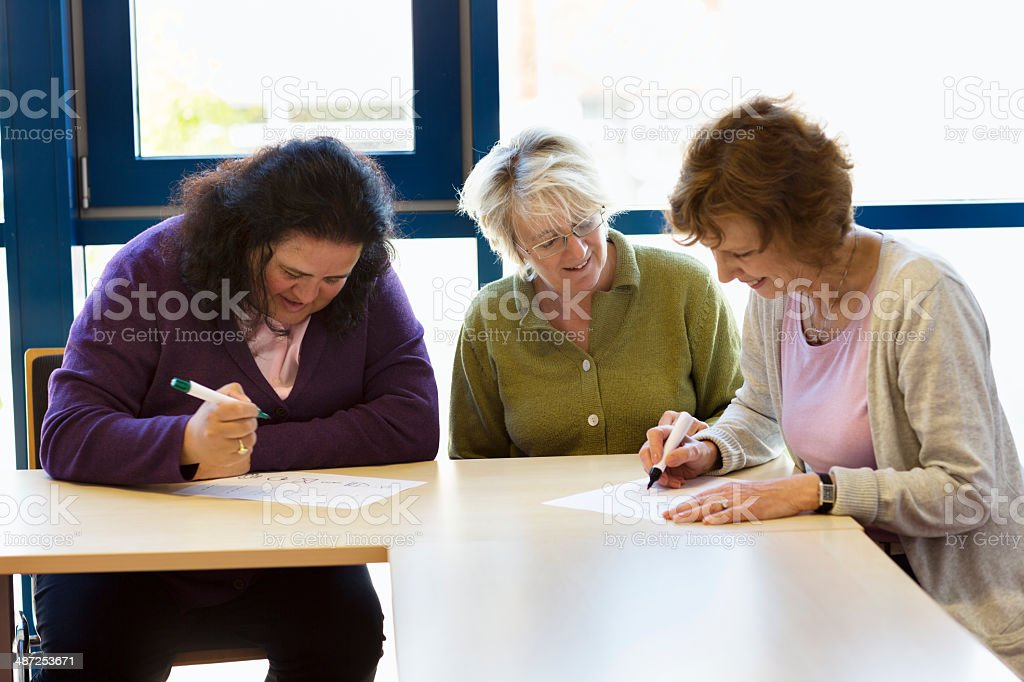 illiterate women learn writing with teacher in classroom stock photo
