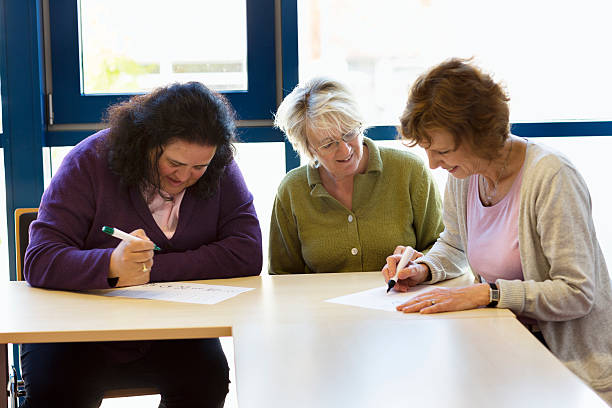 illiterate women learn writing with teacher in classroom illiterate women learning how to write with the support of  a teacher in classroom illiteracy stock pictures, royalty-free photos & images