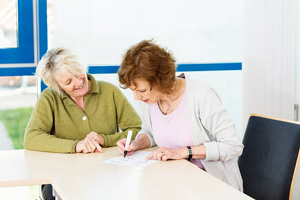 illiterate women learn writing with teacher in classroom illiterate woman practising writing with the help of a  teacher in classroom, learning material in german language illiteracy stock pictures, royalty-free photos & images