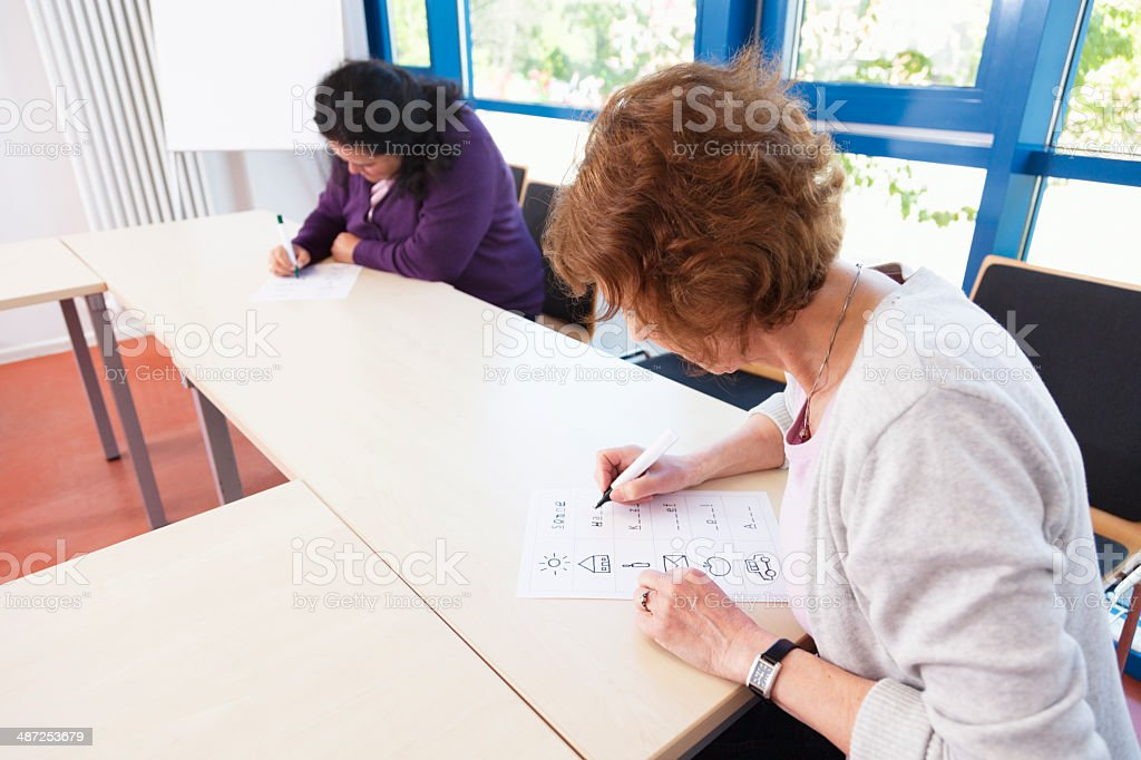 illiterate women learning to write stock photo