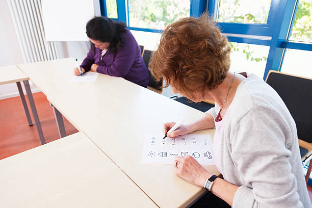 illiterate women learning to write illiterate women learning to write, sitting in classroom, learning material in german language illiteracy stock pictures, royalty-free photos & images