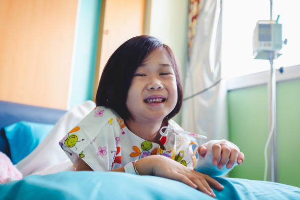 Illness asian child admitted in hospital while saline intravenous (IV) on hand. stock photo