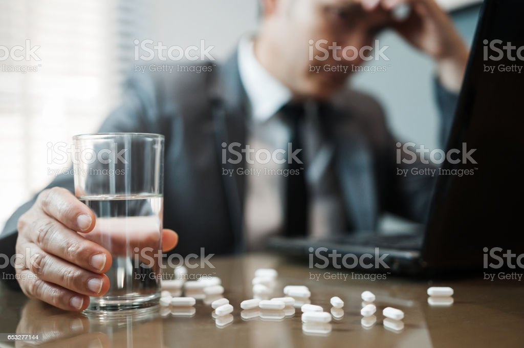 Illness, stressed, tired, exhausted, pain from overworked concepts. Asian Businessman holding glass of water with pills. Man has  migraine. stock photo