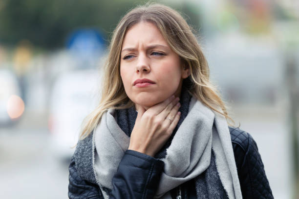 Illness young woman with terrible throat pain walking to the street. Shot of illness young woman with terrible throat pain walking to the street. throat stock pictures, royalty-free photos & images
