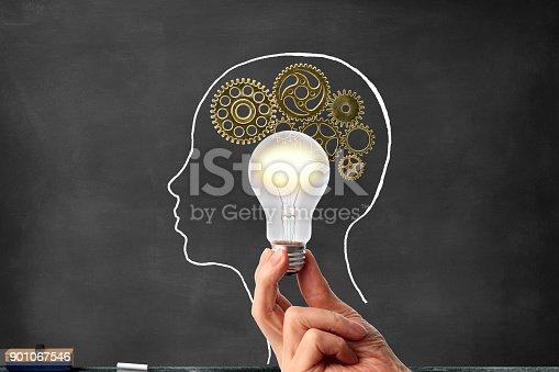 istock Illuminated a light bulb in front of drawn human head on a blackboard 901067546