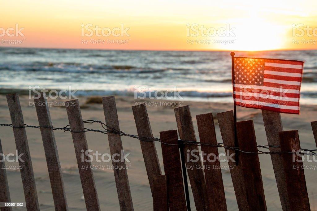 illuminated American flag on beach fence stock photo