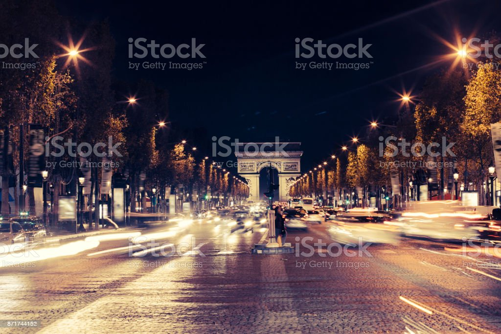 Illuminated Arc de Triomphe and the avenue Champs-Elysees in Paris. Famous touristic places and transportation concept. Night urban landscape with street traffic and city lights. Long exposure. Toned stock photo