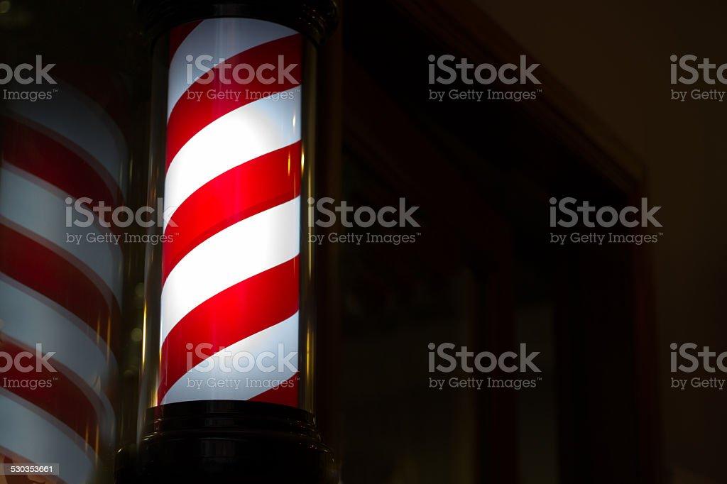Illuminated Barbershop Pole Against Black (Close-Up) stock photo