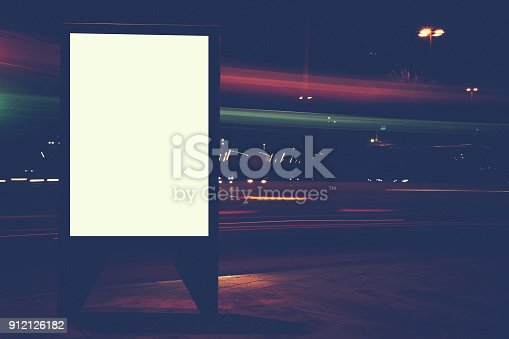 istock Illuminated blank billboard with copy space for text message or content, public information board in night city with cars light on background, advertising mock up banner, clear poster on roadway 912126182