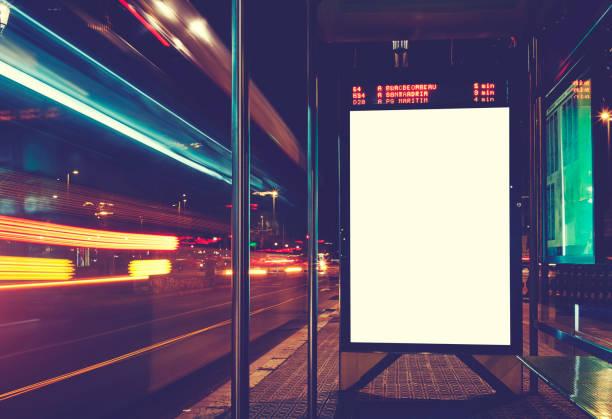 verlichte leeg bord met kopie ruimte voor uw sms-bericht of de inhoud, reclame mock up banner van busstation, openbare informatiebord met wazig voertuigen in hoge snelheid in nacht stad - bushalte stockfoto's en -beelden