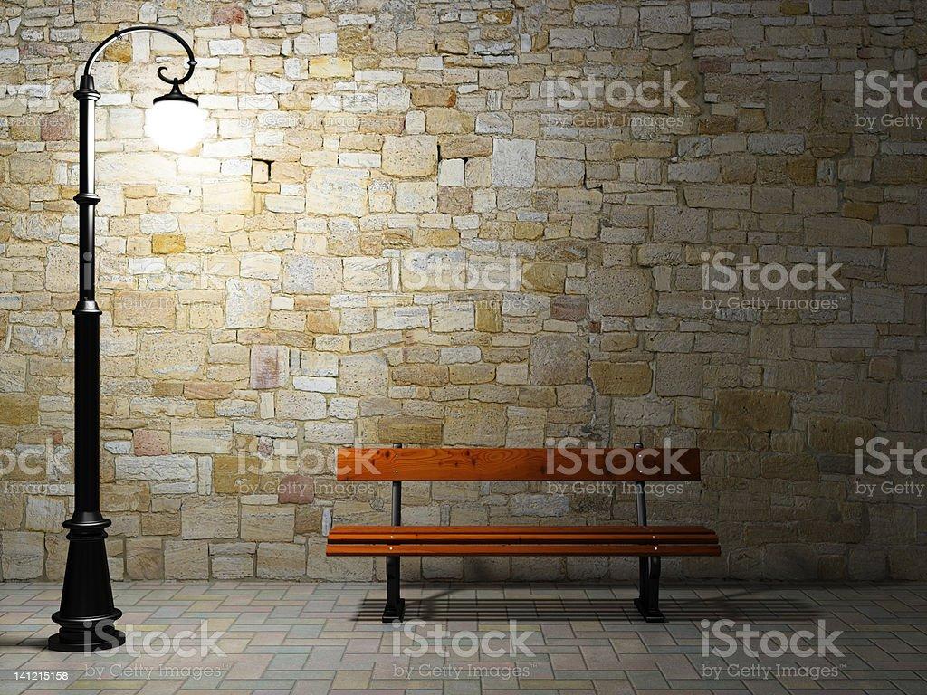 Mur en brique illuminé avec vieux feu et banc de musculation - Photo