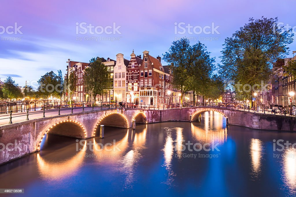 Illuminated Bridges and Canal Houses in Amsterdam Netherlands stock photo
