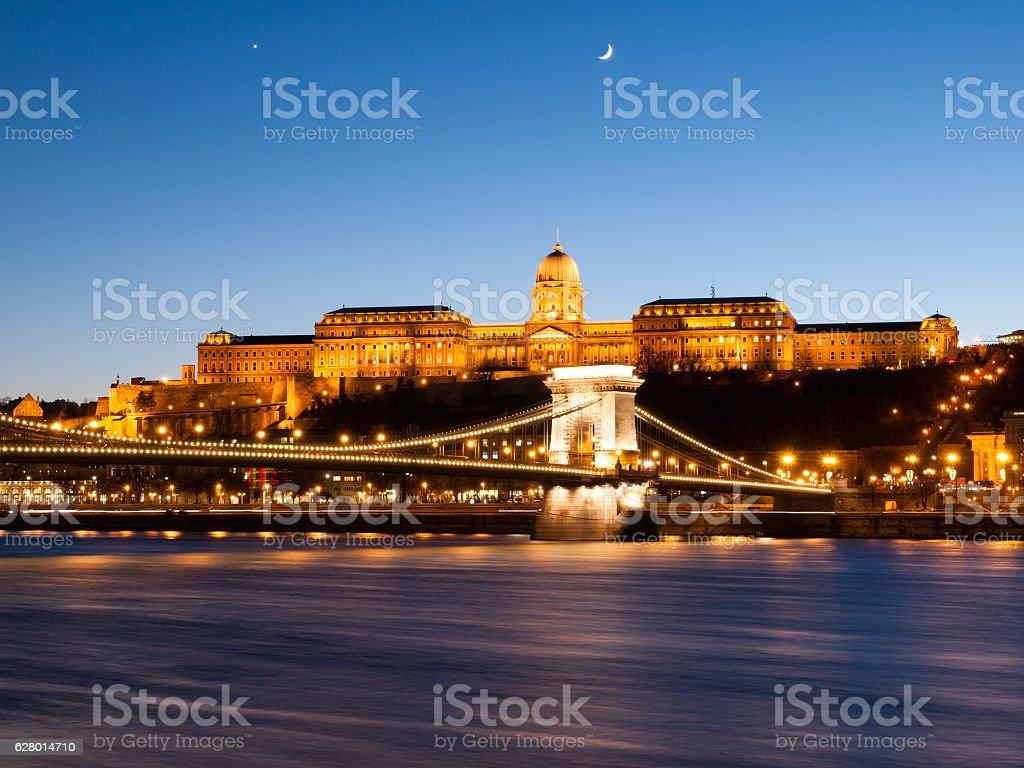 Illuminated Buda Castle and Chain Bridge over Danube River in stock photo