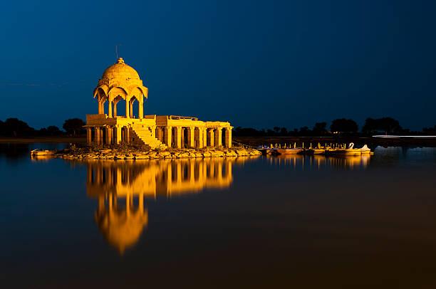 illuminated building at gadsisar lake, jaisalmer, rajastan, india - mahroch stock pictures, royalty-free photos & images