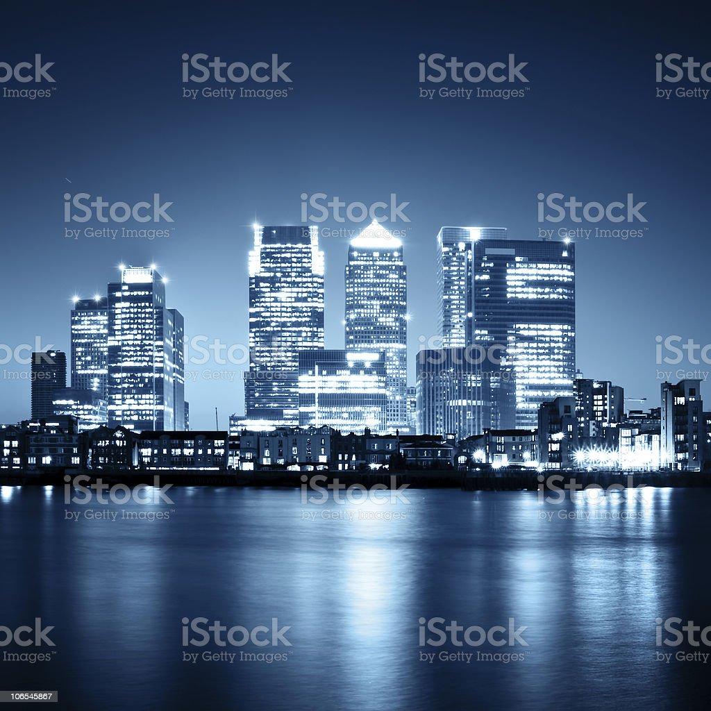 Illuminated Canary Wharf skyline in London at night stock photo