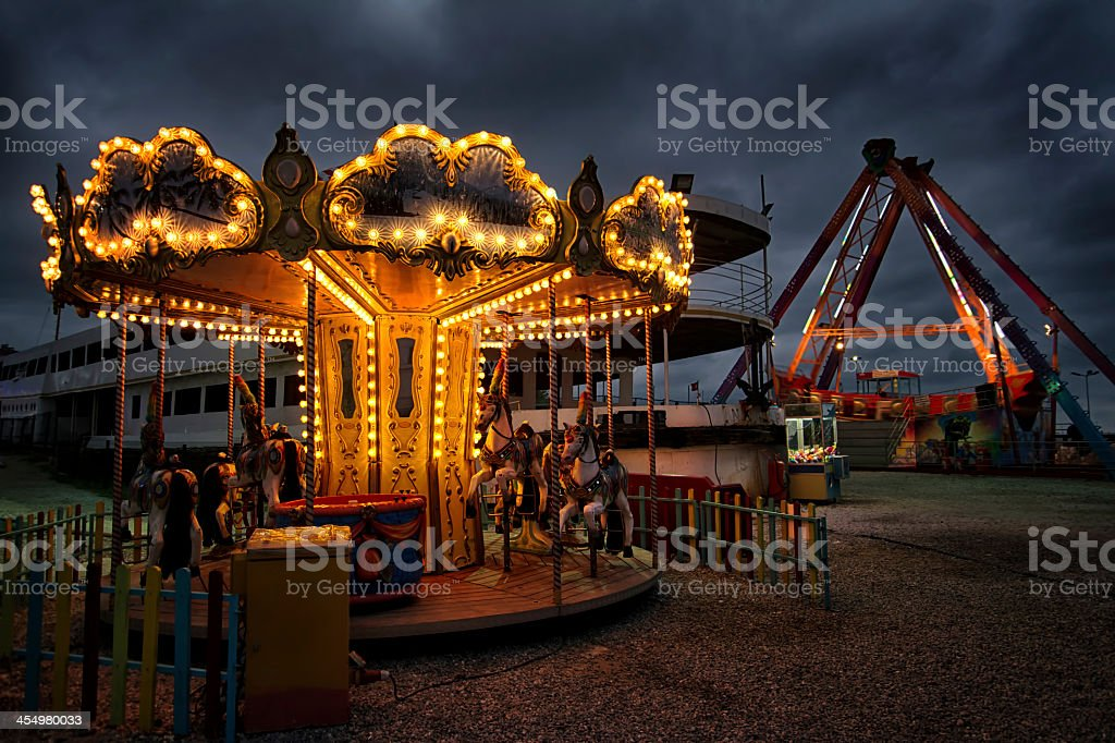 Illuminated carousel in an empty carnival stock photo
