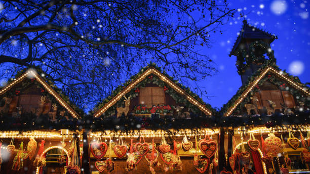 beleuchteter weihnachtsmarkt in der nacht - christkindlmarkt stock-fotos und bilder