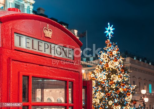 Classic red telephone booth in front of a colourful decorated festive Christmas tree with holiday lights at night in Regent Street in Central London, England, UK