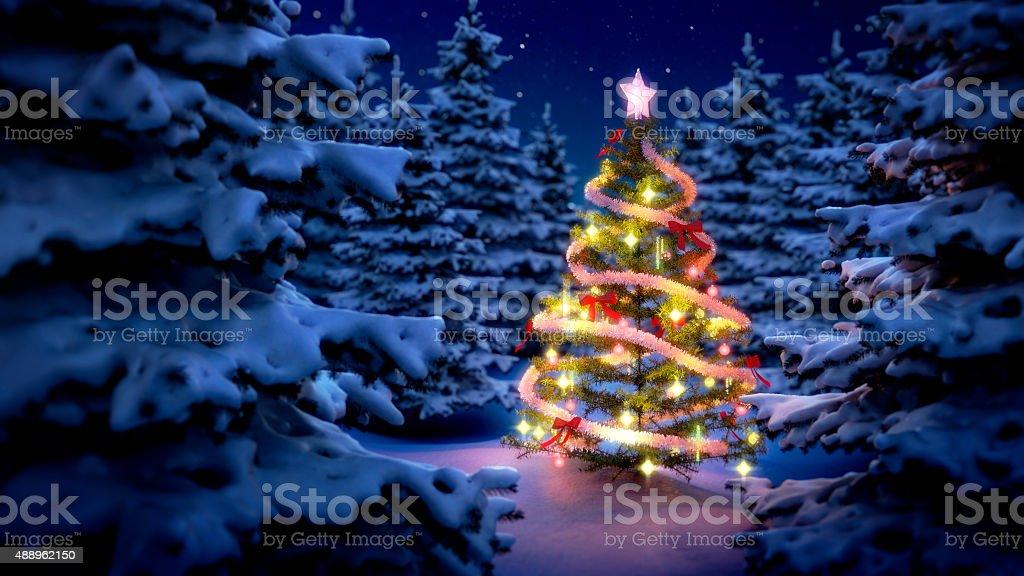 illuminated christmas tree in pine woods stock photo