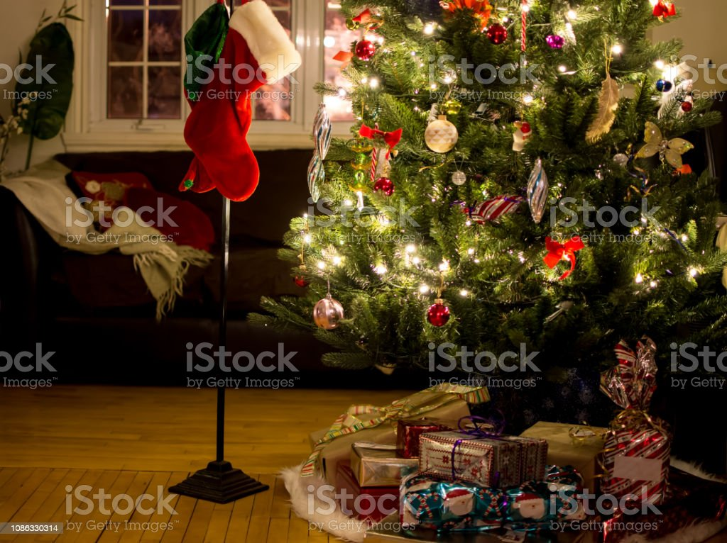 Illuminated Christmas tree with gifts in cozy home holiday background stock photo