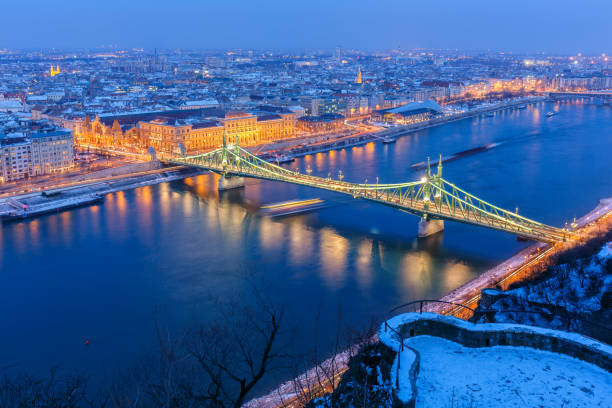 Illuminated cityscape of Budapest with snowy winter landscape at dusk Budapest cityscape with Liberty Bridge on Danube at dusk liberty bridge budapest stock pictures, royalty-free photos & images