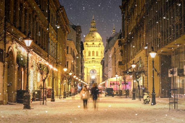 illuminated cityscape of zrinyi street in budapest with st stephen's basilica in a snowy winter landscape at dusk - cultura europea foto e immagini stock