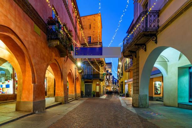 Illuminated cobblestone street in old town of Alba. stock photo