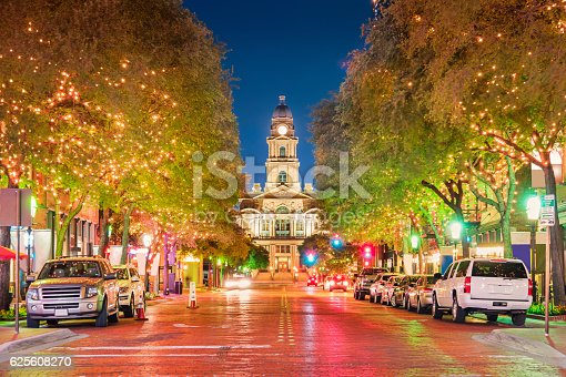 Photo of string light illuminated trees and colorful city street in downtown Fort Worth, Texas, USA, with the Tarrant County courthouse building in the background.