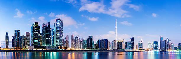 Illuminated Dubai city skyline at sunset, United Arab Emirates. stock photo