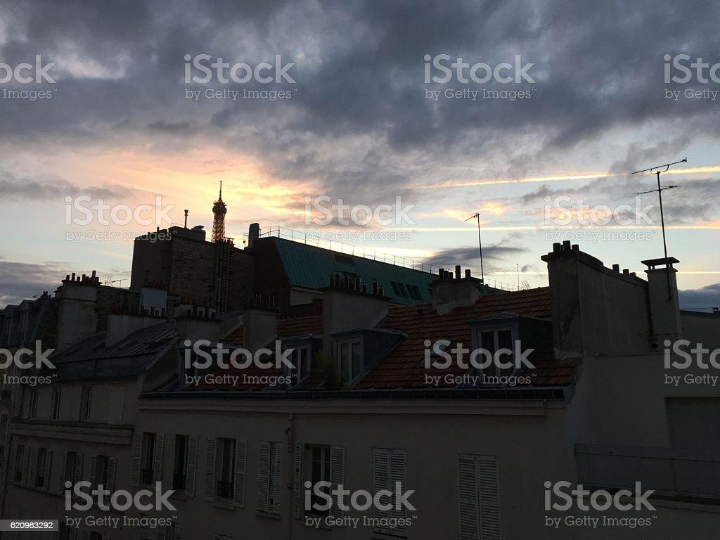 Illuminated Eiffel Tower over Parid roofs foto royalty-free