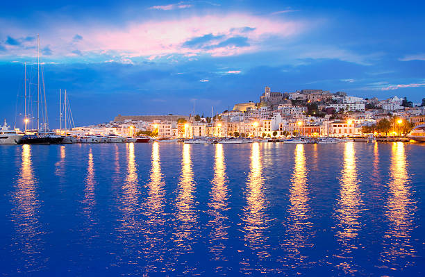 Illuminated Eivissa town at night as seen from Ibiza island stock photo