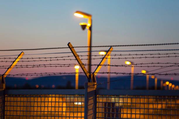 Beleuchteter Zaun und Rasierdraht in der Dämmerung – Foto