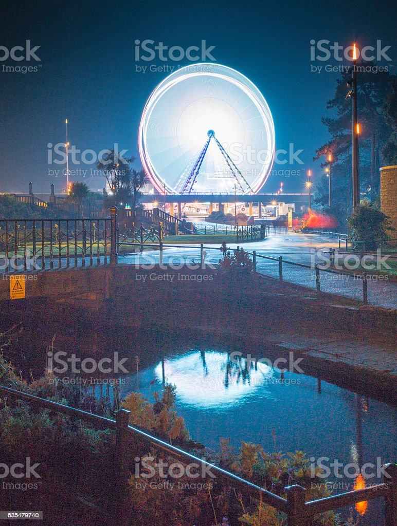 Illuminated Ferris Wheel reflected in a steam stock photo