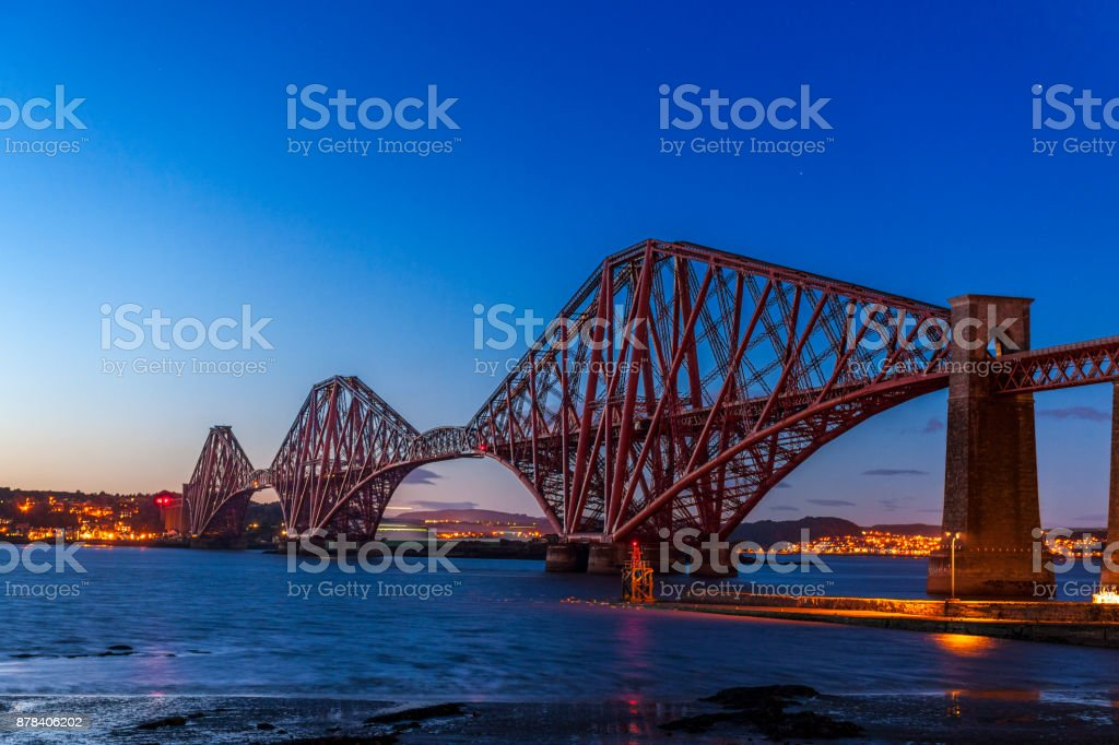 illuminated Firth of Forth Rail Bridge at dusk in Edinburgh Scotland UK. This image is GPS tagged stock photo
