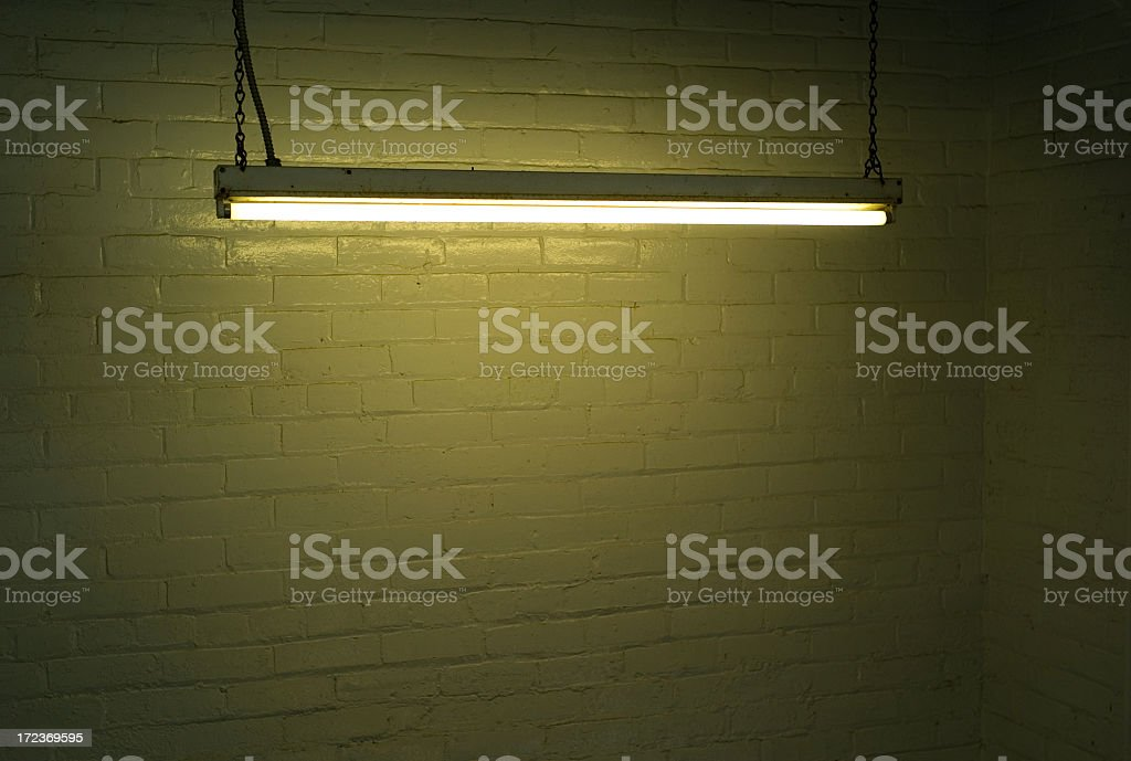 Illuminated fluorescent strip light against brick wall stock photo