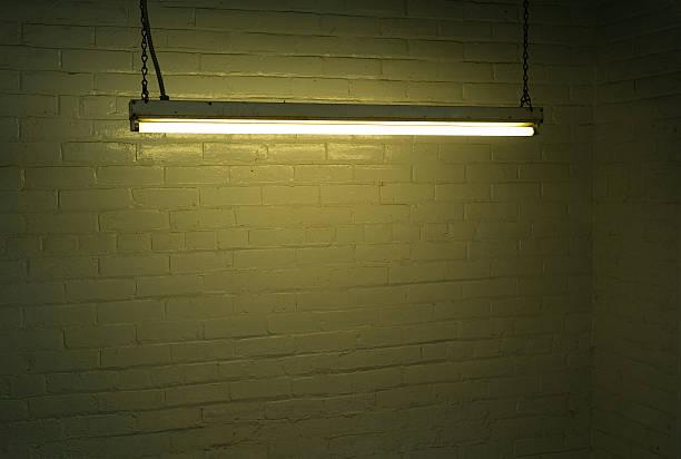 Illuminated fluorescent strip light against brick wall stock photo