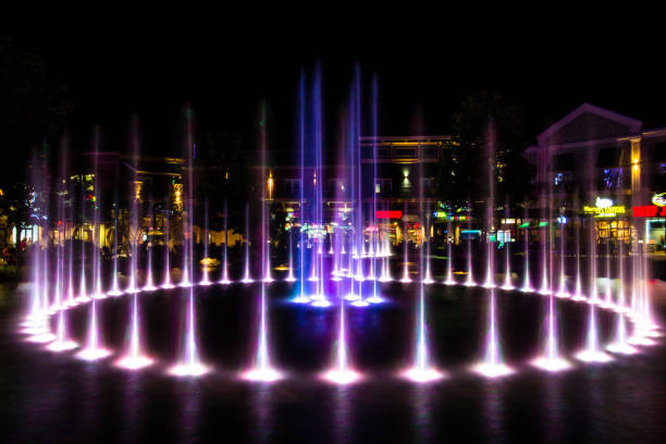 Illuminated Fountain At The ISland In Pigeon Forge Pigeon Forge, Tennessee, USA - May 15, 2017: Illuminated musical fountains at the Island entertainment complex in the Tennessee resort town of Pigeon Forge. pigeon forge stock pictures, royalty-free photos & images