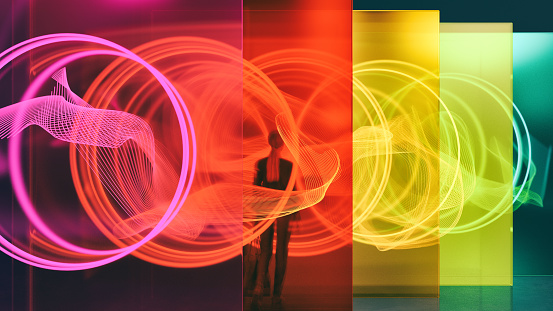 A person standing among glass walls illuminated by glowing rings. All objects in the scene are 3D