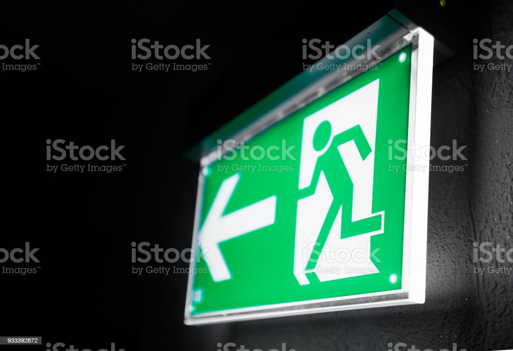 Modern green emergency exit sign above a black doorway