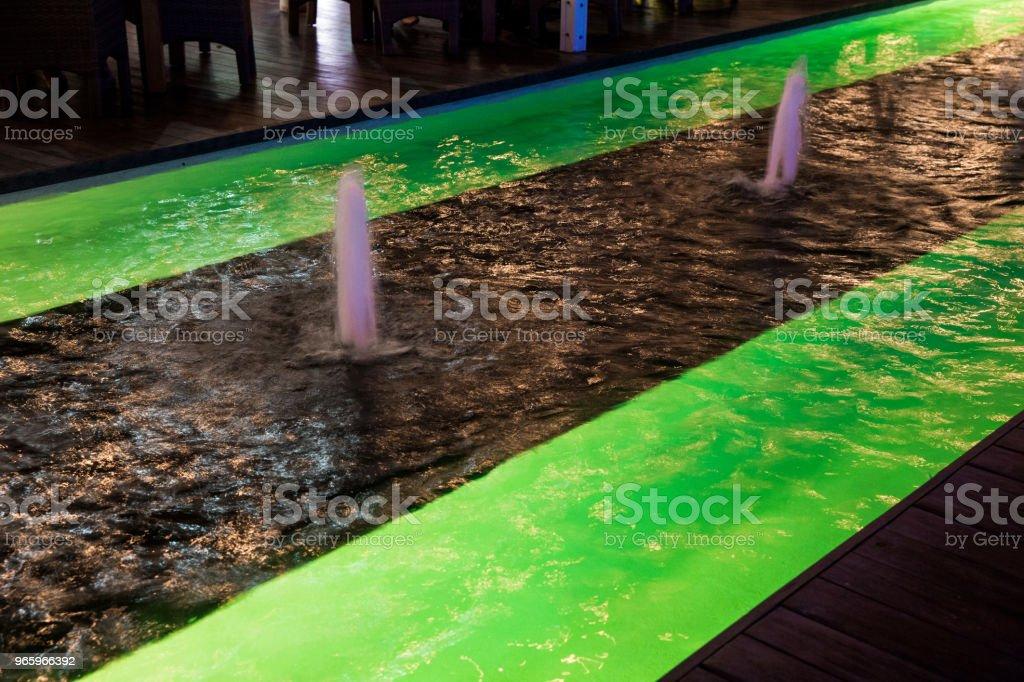 Освещенный зеленый светодиодный свет рядом с фонтаном - Стоковые фото Абстрактный роялти-фри