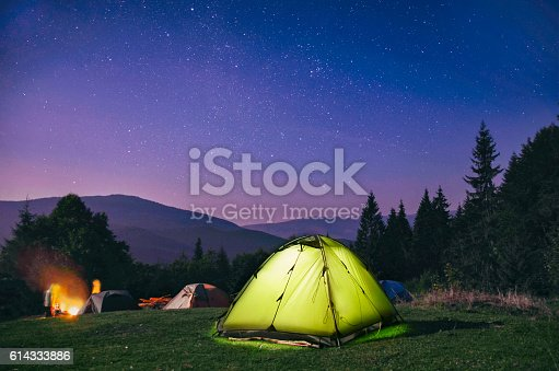 Illuminated  green  tent under stars at night  forest , Carpathian ,Ukraine