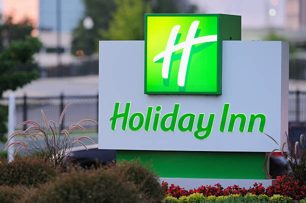 Illuminated Holiday Inn sign at dusk stock photo