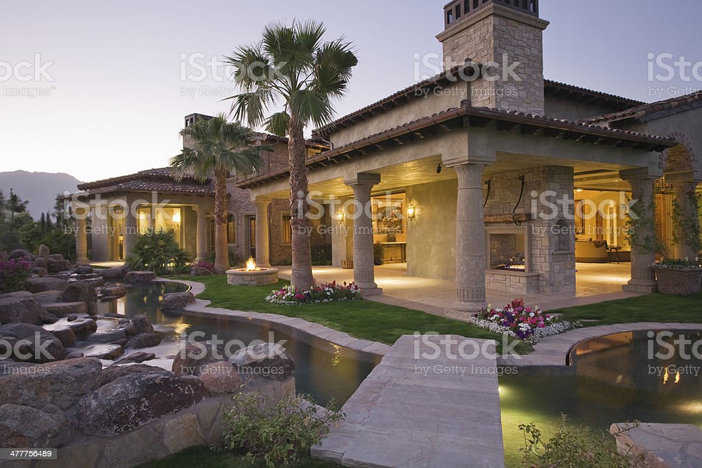 Illuminated House With Pond In Foreground stock photo