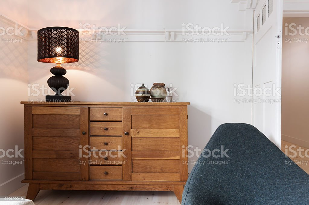 Illuminated lamp on sideboard buffet in living room stock photo