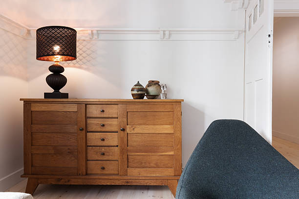 illuminated lamp on sideboard buffet in living room - sideboard weiß holz stock-fotos und bilder