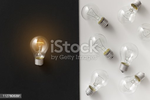637573406 istock photo Illuminated lamp separated from other on contrast background 1127805391