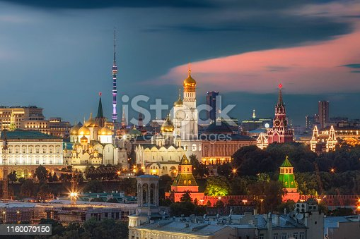 Aerial view of illuminated Kremlin landmarks (Ivan the Great bell tower, Spasskaya tower, GUM), highlighted government palaces and tall Ostankino tower on the background