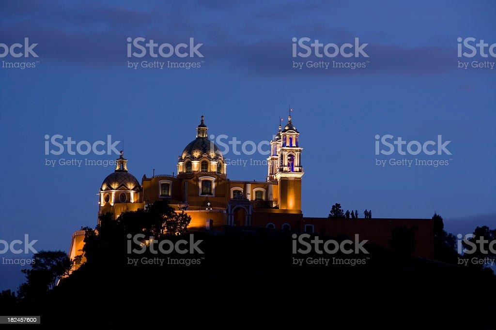 Illuminated large Catholic Church on a hill at dusk stock photo