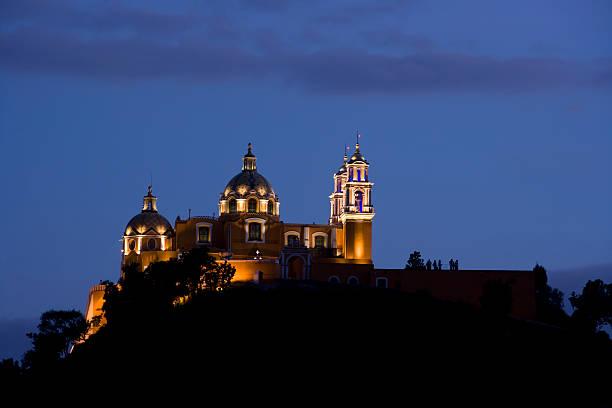 Illuminated large Catholic Church on a hill at dusk Cholula Catholic Church puebla state stock pictures, royalty-free photos & images